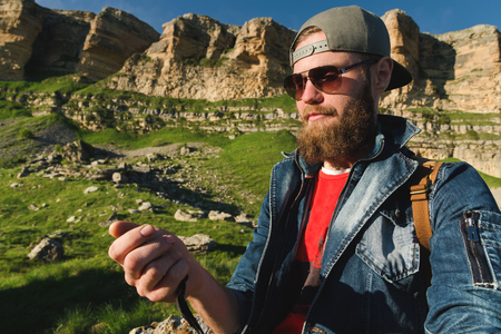 Close-up of a bearded man in jeans clothes in sunglasses and a cap with a backpack sitting at the foot of the epic rocks with a compass in his hands. Navigation travel tourism and orientation Reklamní fotografie