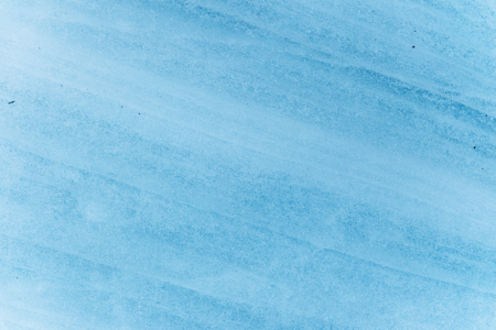 Close-up wall of a centuries-old glacier with a structure of stripes and bubbles. Ice blue light texture