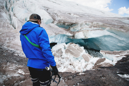 A young guide in a cap with climbing equipment and an ice ax in his hand stands against the background of a crumbling glacier and cracks. The concept of global warming and professional guides