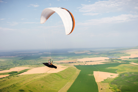 Professional paraglider in a cocoon suit flies high above the ground against the sky and fields Stok Fotoğraf