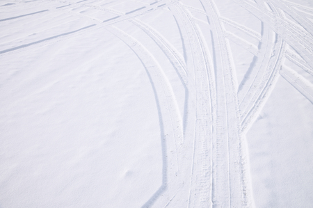 Traces of intersecting arcs of automobile tires in fresh snow