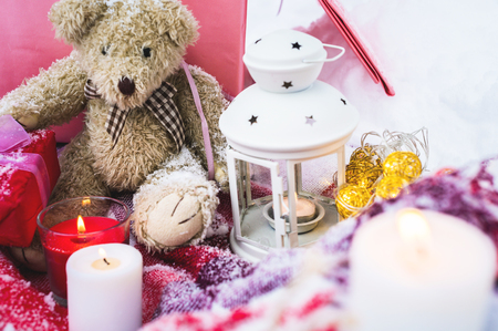 A close-up of a teddy bear with Christmas candles on a cozy checkered plaid outdoors next to a red gift box sprinkled with snow. Christmas festive mood