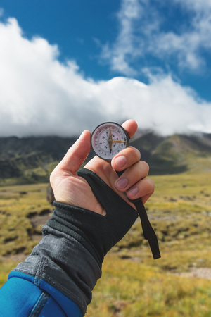 Viewpoint shot. A first-person view of a mans hand holds a compass against the background of an epic landscape with cliffs hills and a blue sky with clouds Banco de Imagens