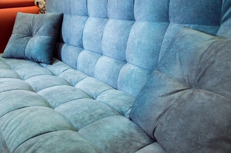 Close-up comfortable blue soft sofa with curly stitching. Modern design Фото со стока