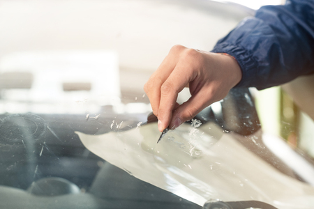 Close up Automobile glazier worker fixing and repair windscreen or windshield of a car in auto service station garage
