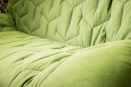 Close-up comfortable green soft sofa with curly stitching. Modern design Фото со стока
