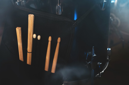 Close-up of drum sticks in a case on one of the drums in a dark studio. The concept of live performances Foto de archivo