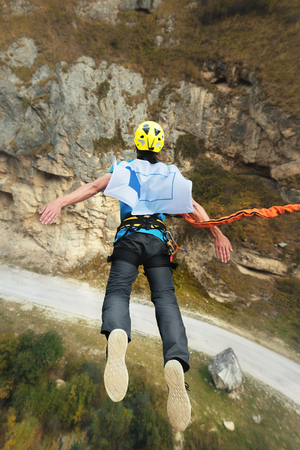 A man in a helmet jumps ropeup with an empty flag in the mountains. Extreme sports. Leisure. Top view Imagens