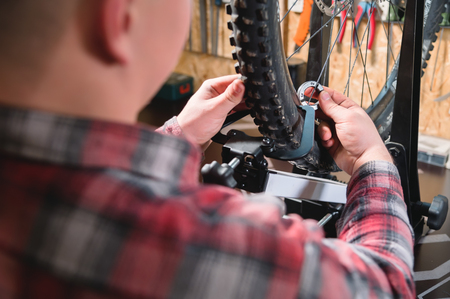 Young male bicycle repairman with a specialized wrench on a stand in the workshop, tightening the spokes of the wheel, eliminating the beating of the rim 스톡 콘텐츠