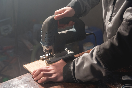 Close up of carpenters hands working power tools for processing wood. Power Jigsaw
