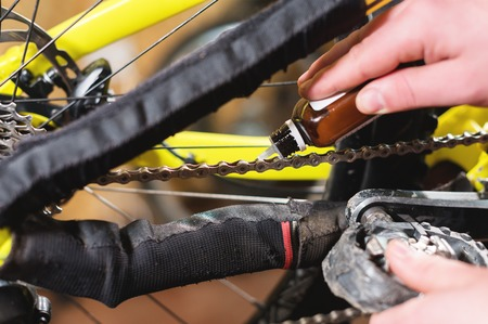 Close-up of mens hands led by masters grease with special grease bicycle chain of mountain bike in the home workshop