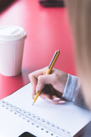 Close-up from behind the back of a young woman in a winter polto is holding a ballpoint pen and is going to write something down in a notebook on a red table. Notes.