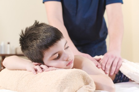 Close up A little boy relaxes from a therapeutic massage. Male massage therapist makes a medical massage to the back of a child