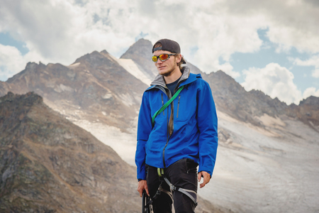 Portrait of a professional guide of a mountaineer in a cap and sunglasses with an ice ax in his hand against the background of the sky and the snow-capped mountains of the Caucasus