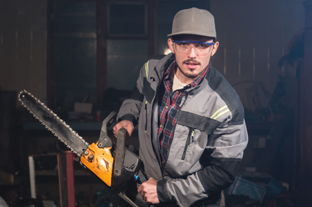 Portrait of a young carpenter holding in his hands a chainsaw threatening the viewer with threats. Security breach. Jokes