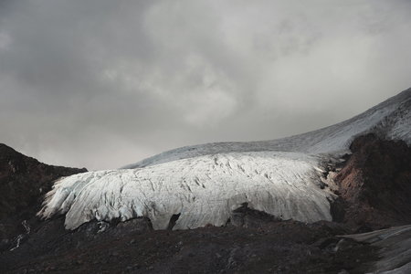Mountain landscape dusty dirty volcanic slope with cracked melting glacier. Global warming. Glaciers of North Caucasus