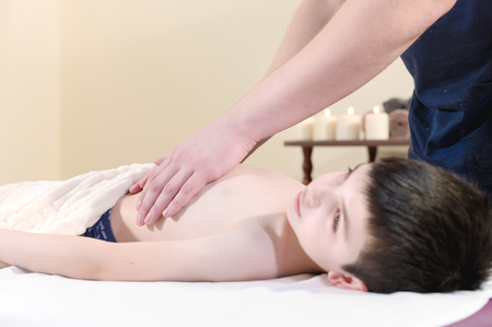 A little boy at the reception at a professional masseuse. Male manual worker gives massage to the front of the child