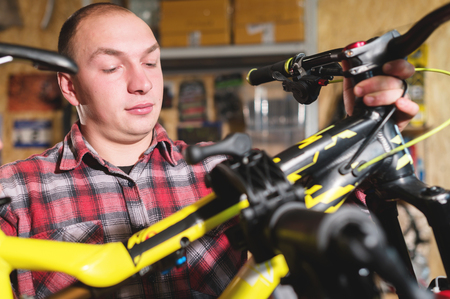 Portrait of a bicycle master in a workshop installing a mountain bike on a diagnostic stand