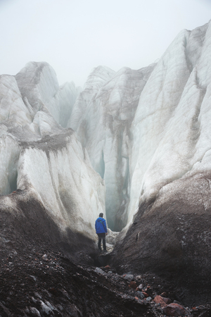 A free climber with an ice ax stands at the foot of the Great Glacier next to an epic crack in the fog in the mountains. Insurmountable obstacle