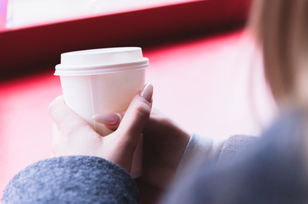 Beautiful girl hands hold paper cup with a drink Stock Photo