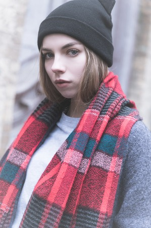 cold portrait of a young attractive girl in a cap coat and red scarf in the cold season