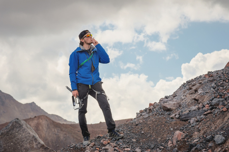 Portrait of a professional guide-mountaineer in a cap and sunglasses with an ice ax in his hand smoking a cigarette against the sky and the snow-capped mountains of Caucasus. The problem of smoking