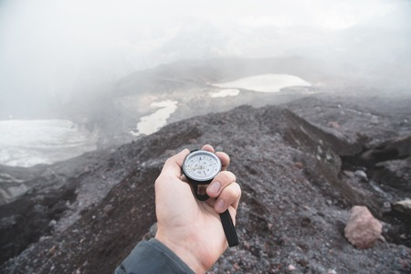 A first-person view of a mans hand holding a magnetic compass against the background of the snow-capped mountains of the Caucasus and mountain lakes. The concept of finding destinations and traveling Stock Photo