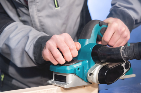 Close-up of a carpenters hand working with an electric plane with suction of sawdust. Leveling and sanding wooden bars Stock Photo