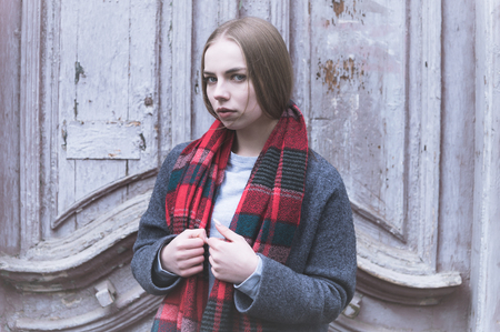 Cold portrait of a young offended attractive girl in a coat and red scarf in the cold season on the background of an old vintage door