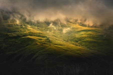 Low evening sunlight at dusk illuminates the hilly green hillsides and low clouds. Nature of the North Caucasus Stock Photo