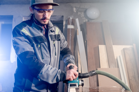 Portrait of a young carpenter working with an electrical plane in a home wood workshop. The concept of a business idea and a woodworking startup Reklamní fotografie