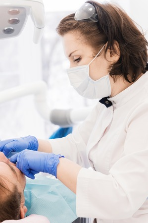 Aged man at the reception at the dentist. Woman doctor examines the patients mouth