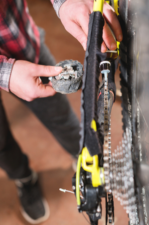 Close-up of mens hands led by masters grease with special grease bicycle chain of mountain bike in the home workshop Reklamní fotografie - 120184755