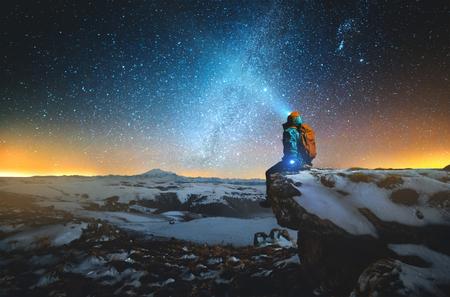 Nachtwinterlandschaft Ein Mann mit Rucksack und Laterne auf dem Kopf sitzt im Winter auf einem Felsen in den Bergen vor dem Hintergrund eines Berges und eines Wintersternenhimmels und der Milchstraße