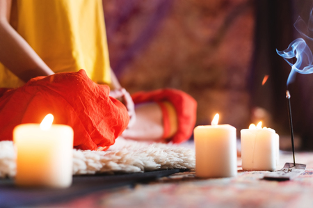 Close-up of womans hand in yoga lotus pose meditating in a crafting room with candles