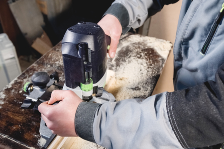 Close-up electric milling cutter in the hands of a worker in a home workshop. Starting a business. Craftsman