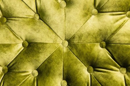 Velor lime surface of sofa close-up. Training equipment-velor mats tightened with buttons. Yellow chesterfield style quilted upholstery background Imagens