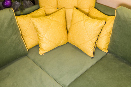 Close-up green corner sofa with yellow pillows. Textile new furniture modern design