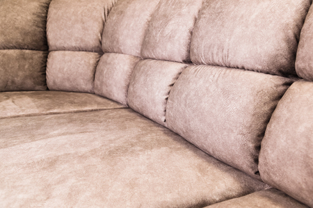Close-up of an expensive soft textile sofa of beige color with brown shades. Interior Background