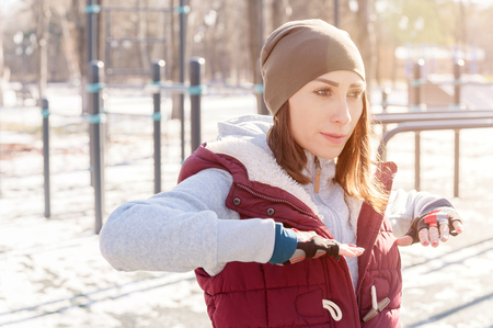 Sports girl in warm clothes on a sunny day does a warm-up on the outdoor sports field in the winter in spring or autumn during the cold season on the background of bars and horizontal bars