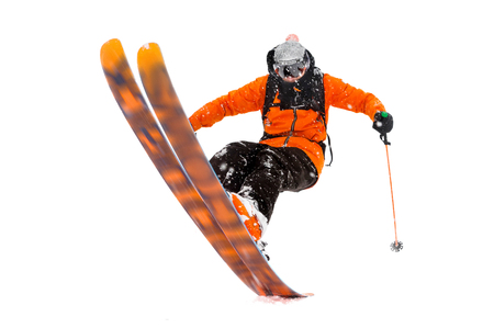 The athlete skier in the orange black suit does the trick on the back of the skis. real photo made in the mountains isolated on white background Foto de archivo
