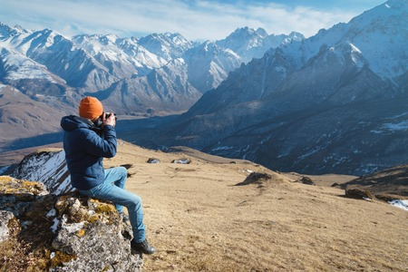 Portrait of a bearded male photographer in sunglasses and a warm jacket with a backpack sits on a big stone and takes pictures on camera against the background of snow-capped mountains