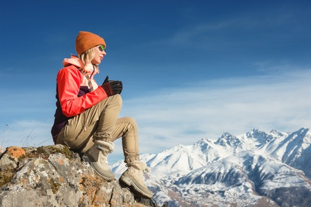Portrait of a beautiful girl in a hat and sunglasses with a mug in her hands is drinking coffee or tea while sitting on a stone in the mountains. The concept of tourism and recreation in the mountains
