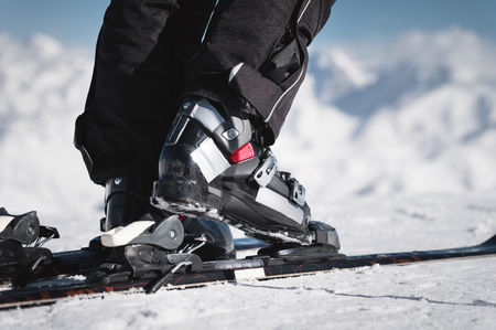 Close-up of the athletes skiers foot in ski boots rises into the skis against the background of the snow-capped Caucasus mountains on a sunny day. Winter sports concept