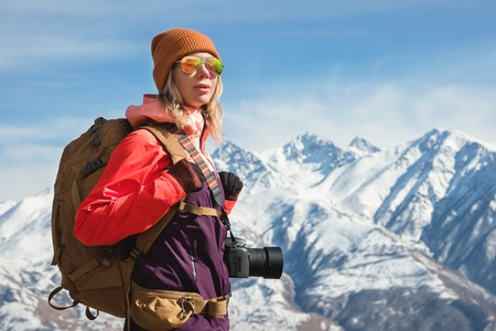 Portrait of photographer hipster tourist girl with a camera in sunglasses and a hat against the background of snow-covered Caucasus mountains. Photo travel concept