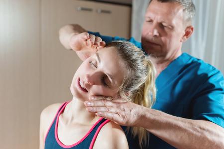 Masajista terapeuta visceral manual masculino trata a una paciente joven. Editando cuello y vértebras