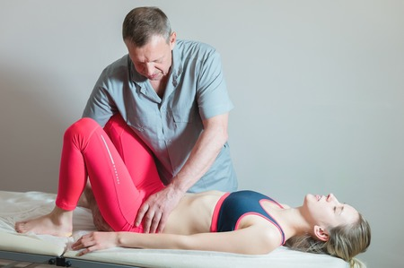 Male manual visceral therapist masseur treats a young female patient. Editing the thigh