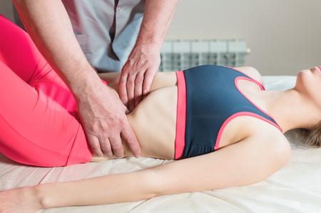 Männlicher manueller viszeraler Therapeut Masseur behandelt eine junge Patientin. Bearbeiten Sie die inneren Organe und beseitigen Sie Verwachsungen im Magen