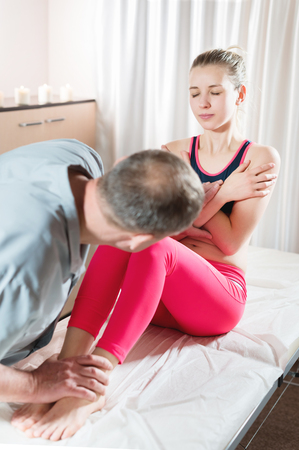 Male manual visceral therapist masseur treats a young female patient. Work with the abs and abdominal muscles 写真素材
