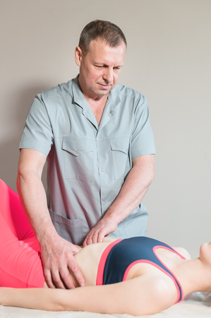 Male manual visceral therapist masseur treats a young female patient. Edit the internal organs and the elimination of adhesions in the stomach